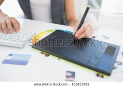 stock-photo-close-up-mid-section-of-a-female-photo-editor-using-graphics-tablet-in-a-bright-office-168159791